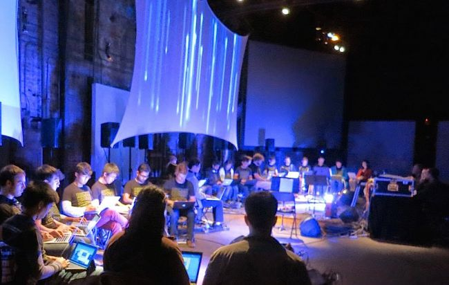 An image of several students using their laptops to form an orchestra on a grand stage.
